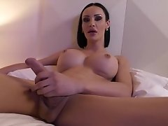 Kimberlee jacks off her massive tranny dong and creams all over the bed in a purple room